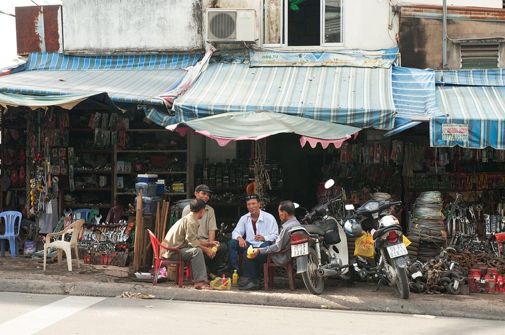 Men socializing on a sidewalk in Ho Chi Minh City, Vietnam