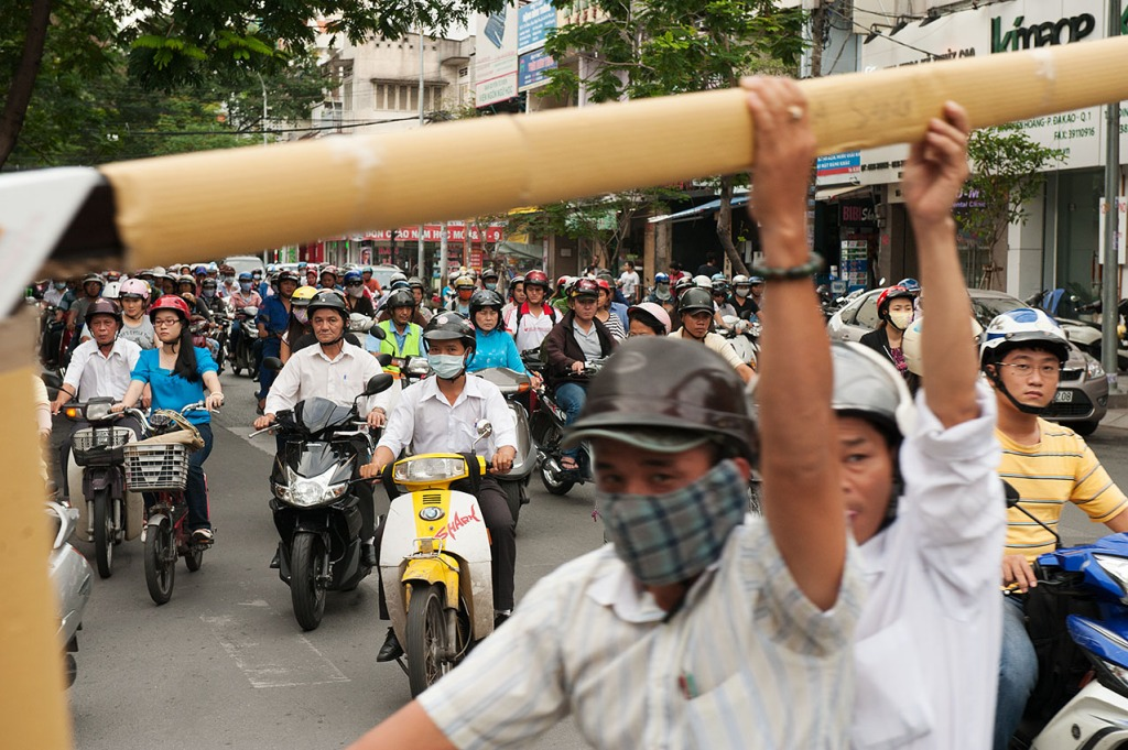 Constant buzzing of mopeds - often carrying the seemingly impossible cargo - in Ho Chi Minh City, Vietnam