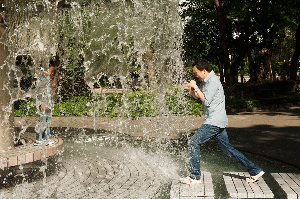 A father gleefully heads toward his son inside the walk-in fountain at Hong Kong Park