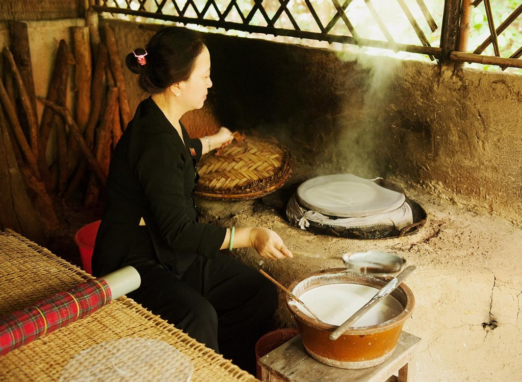 Local woman demonstrating how traditional rice paper for summer rolls is made within seconds
