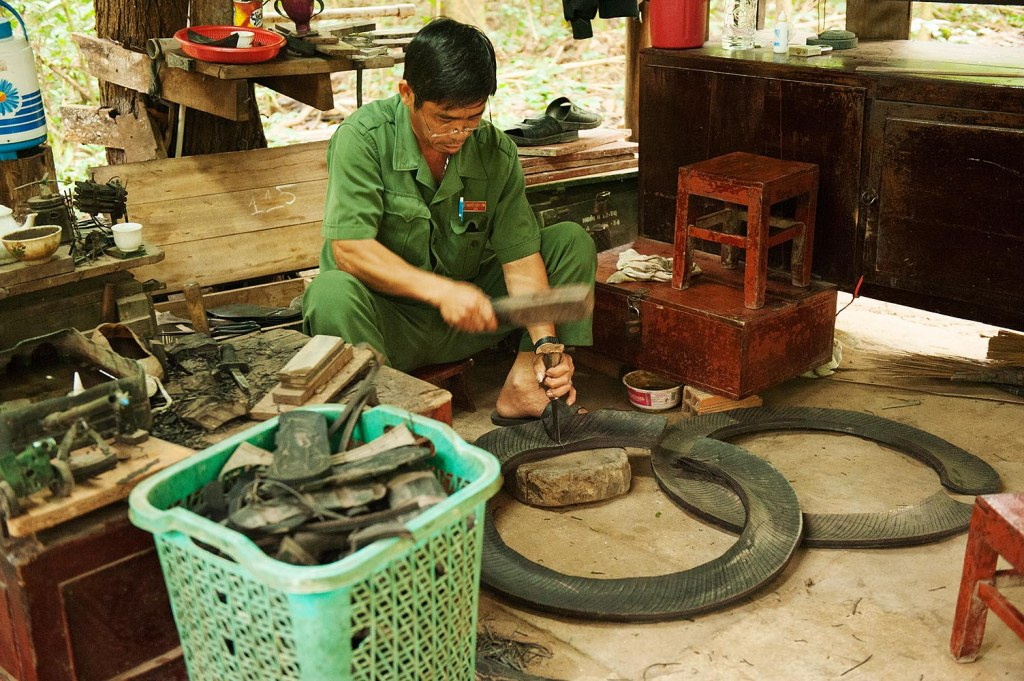 Local worker demonstrating how wartime shoes were made from tires