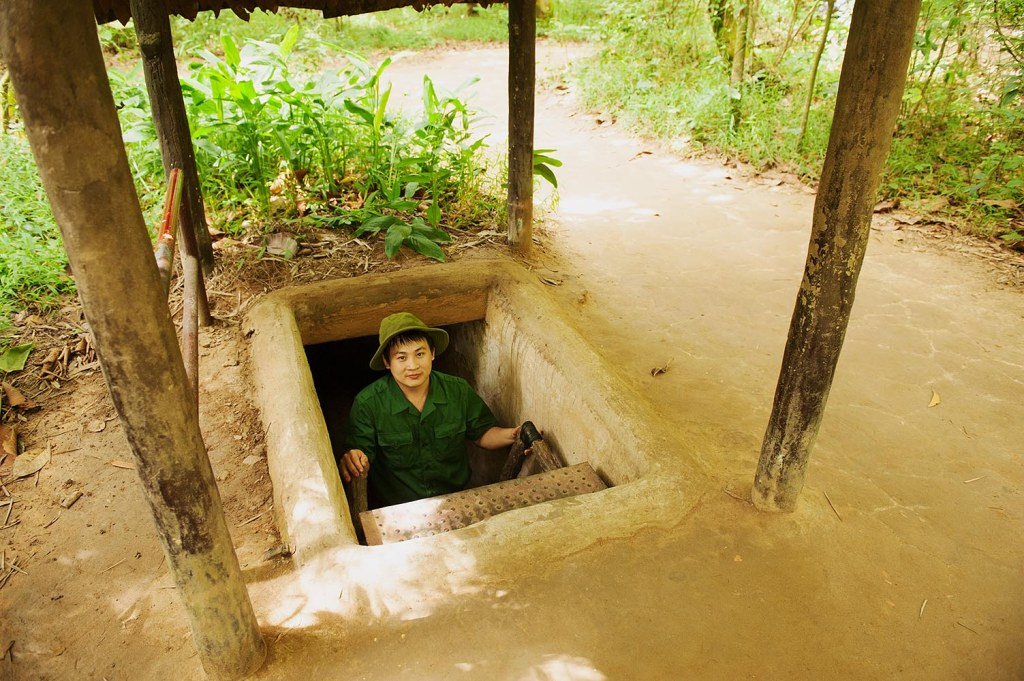 Local worker exiting the elaborate Cu Chi tunnel system