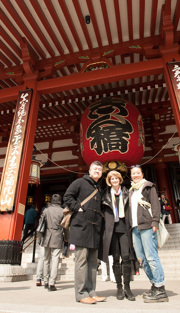 Michele, Satoko, and Takinori, about to toss coins inside the main temple hall at Sensō-ji