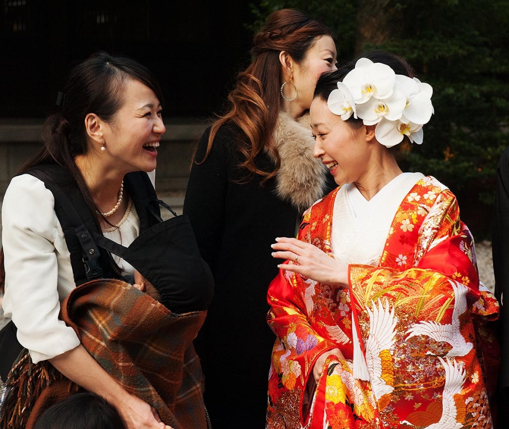 A lovely bride in a brightly colored wedding kimono shares a joyful moment with family and friends