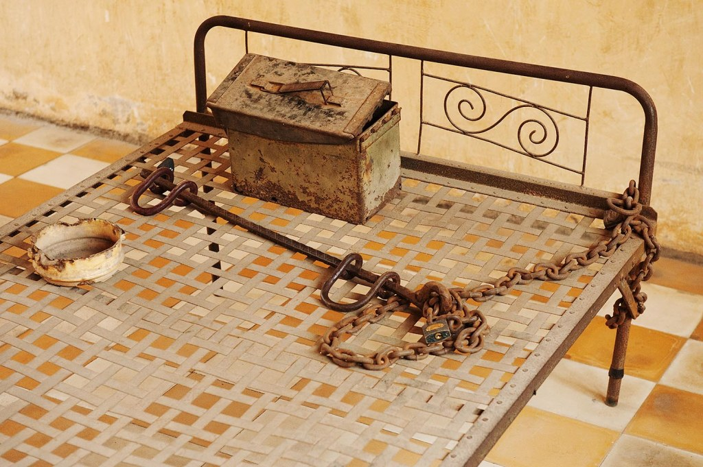 A close-up of one of the metal beds, with foot shackles and a box for waste
