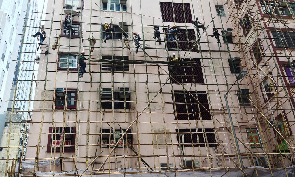Construction workers perched on bamboo scaffolding (note the absence of any real safety equipment!)
