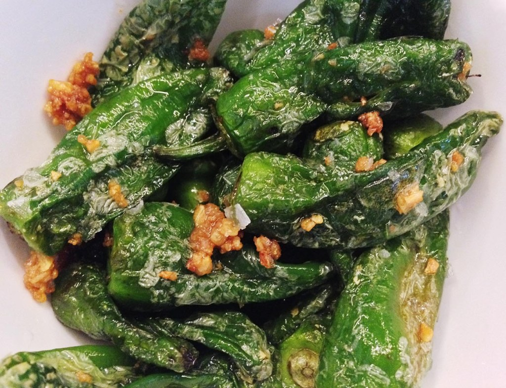 Smoky, spicy padrón peppers, tossed with sea salt and fried garlic, at Ham & Sherry