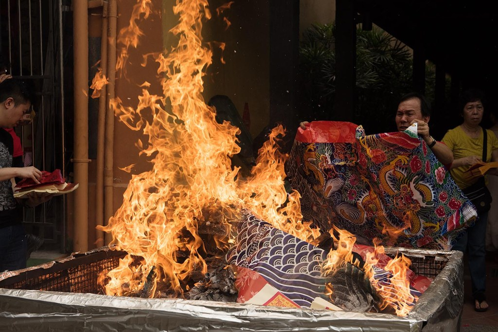 Joss paper burning at a streetside shrine in Chinatown