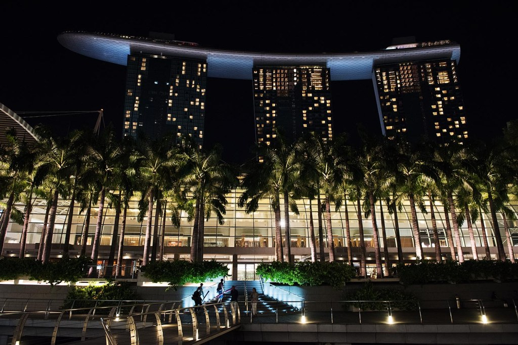 Illuminating the modern, iconic design of Marina Bay Sands, with its Shoppes in the foreground