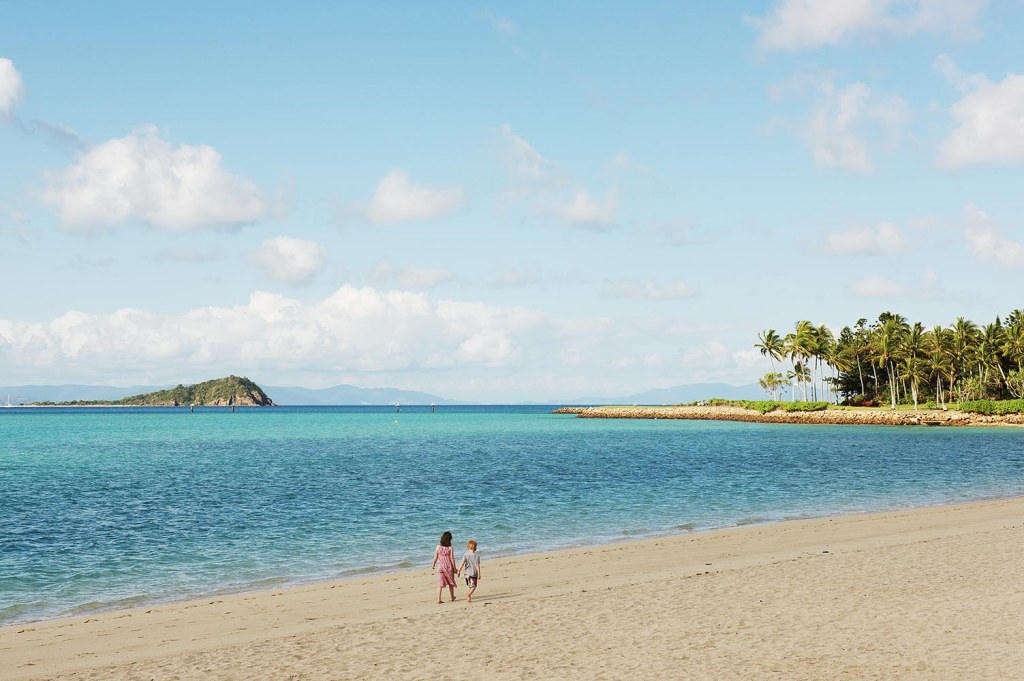 A young brother and sister roam the One & Only Hayman Island private beach