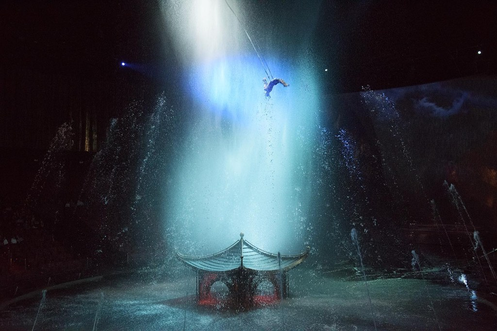 In one of my favorite scenes from the show, a single acrobat swings precariously in the 'rain' over a pagoda that immerses into the massive stage pool before disappearing