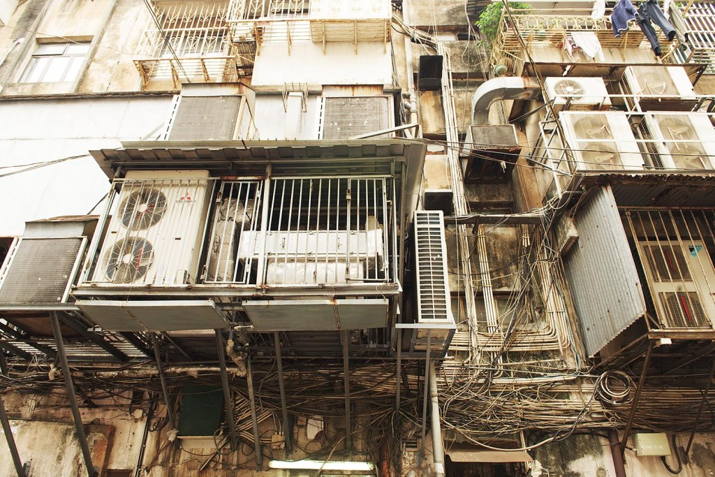 Truth in travel moment: classic backstreet Asia, with a hazardous tangle of wires, cables, machinery, and drying laundry loosely 'organized' on the outside of a building in historic Macau