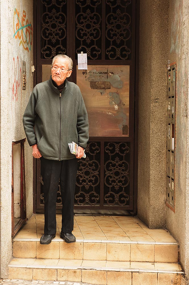 A local gentleman awaits the arrival of family in the historic area of Macau